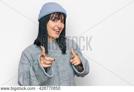Young hispanic woman wearing cute wool cap pointing fingers to camera with happy and funny face. good energy and vibes.