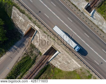 White Truck with Cargo Semi Trailer Moving on Road. Highway intersection junction. Aerial Top View