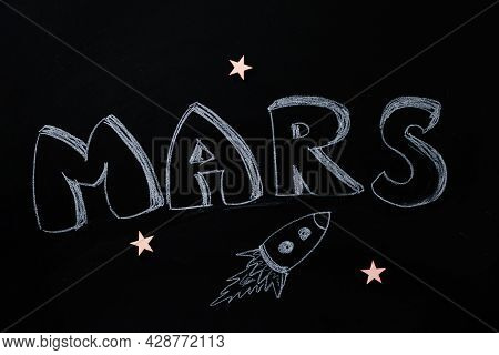 Flight To The Space. Black Chalky Background With The Inscription Mars And Paint Of Flying Rocket. M