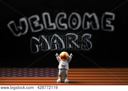 Figure Of Astronaut With Victoriously Raised Hands. In The Background, A Chalky Black Board With The