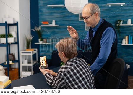 Senior Man Waving At Smartphone Camera During Video Call With Relatives. Happy Grandparents Communic