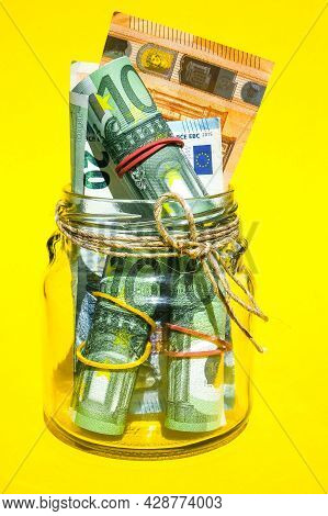 Glass Jars Filled With Euro Bills, Savings Inside Glass Jar, Money Isolated On Yellow Background, Co