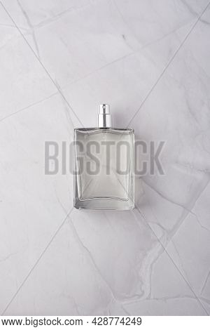 Transparent Bottle Of Perfume With Spray On White Marble Surface. Clear Glass Without Lid. Flat Lay