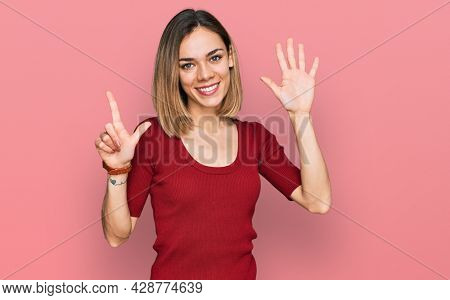 Young blonde girl wearing casual clothes showing and pointing up with fingers number seven while smiling confident and happy.