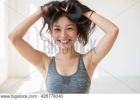 Young beautiful Asian girl smiles and plays with her hair. She is wearing a sporty top and red lipstick. Isolated