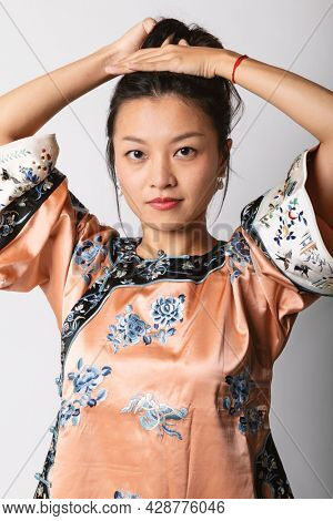 Young Asian girl with a traditional Chinese shirt collects her hair. Studio portrait on white background