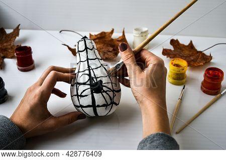 Woman Paints Spider On Pumpkin For Halloween. Autumn Leaves. Diy Children Craft. Do It Yourself. Aut
