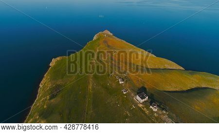 Top View Of Beautiful Sea Cape With Houses On Top. Shot. Stunning Green Cape With Estate On Top Of M