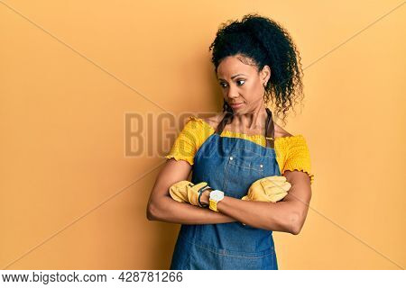 Middle age african american woman wearing professional apron looking to the side with arms crossed convinced and confident
