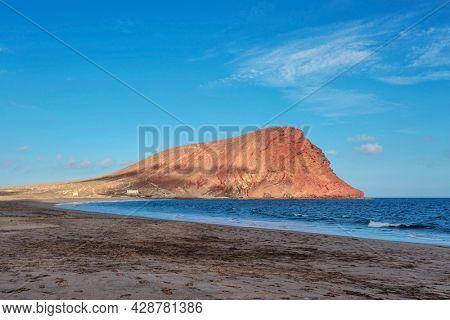 Deserted beach Playa de la Tejita with red mountain Montana Roja, Tenerife, Spain