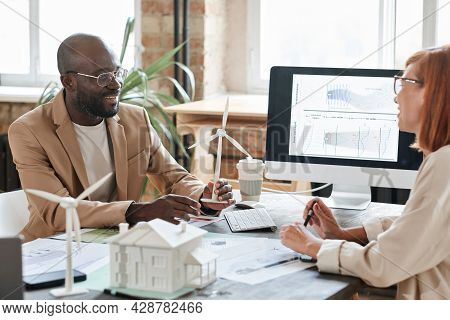 Two Business Partners Sitting At The Table During A Meeting And Discussing New Design Project With M