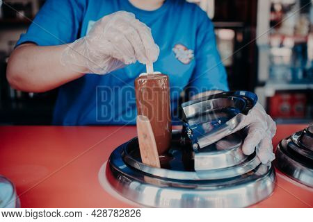 An Ice Cream Vendor Dips A Popsicle In Liquid Chocolate