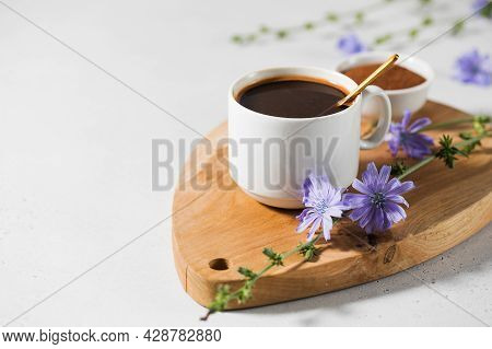 Chicory Drink In A White Mug With Chicory Flowers Next To It On A Wooden Board.