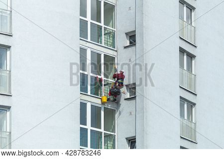 A Man Washes Windows In A Multi-storey Building. Professional Window Cleaning. A Climber Washes A Wi