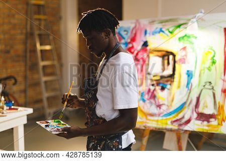 African american male painter at work holding paints and brush in art studio. creation and inspiration at an artists painting studio.
