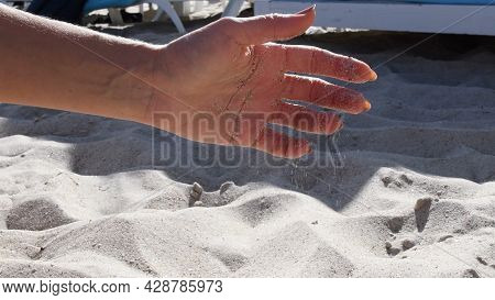 Woman Hand Straighten And Spread Fingers Of Hand Palm. Female Hand Playing With Sand At Sea Beach In