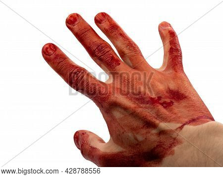 The Man's Hand And Fingers Are Covered With Drops And Splashes Of Blood. The Concept Of The Victim O
