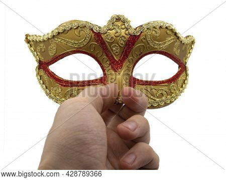 A Man Holds In His Hand A Traditional Golden Carnival Venetian Mask With A Red Ornament On A Black B