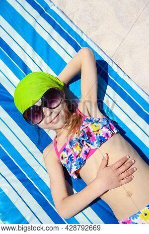 Happy Child In Glasses Sunbathing On The Seashore Background