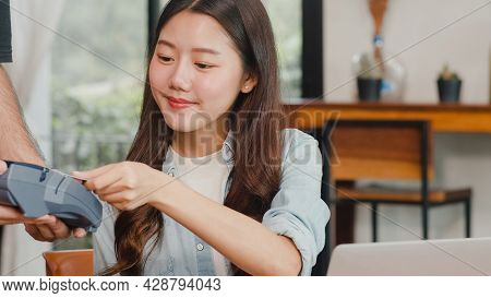 Young Asian Freelance Women Pay Contactless Credit Card At Coffee Shop. Asian Happy Men Barista Wait