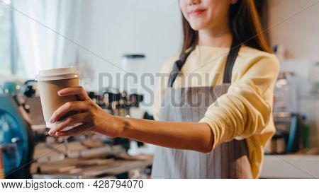 Young Asia Female Barista Serving Take Away Hot Coffee Paper Cup To Consumer Standing Behind Bar Cou