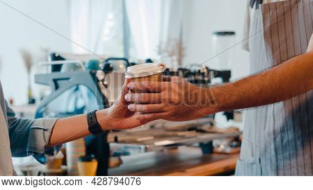Young Asia Male Barista Serving Take Away Hot Coffee Paper Cup To Consumer Standing Behind Bar Count