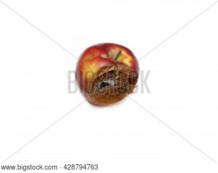 One Rotten,half-decomposed, Darkened, Limp Fruit On A White Background. The Concept Of Expired Food,