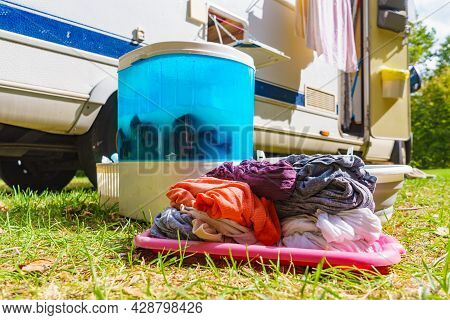 Doing Laundry Outdoor At Caravan. Bowl With Clean Clothes And Washing Machine Working. Camping On Ca