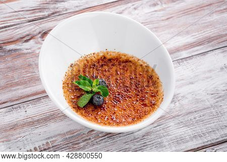 Creme Brulee With Sugar Crust On A White Plate On Wooden Background. Close Up. Macro Photo