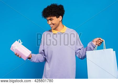 Joyful African American Man In Lilac Pullover Standing With Shopping Bags And Gift Isolated On Blue