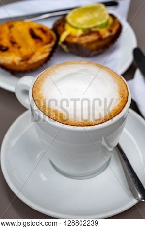 Cup Of Cappuccino Coffee Served With Traditional Dessert Pastry In Portugal, Nata Eggs Cream Cakes W