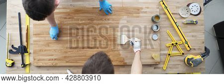 Two Male Construction Workers Are Covering Wood Floor With Protective Layer Of Varnish