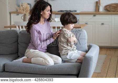 Loving Mother Trying To Make Peace With Stubborn Offended Boy Kid Sitting Frowning And With Crossed
