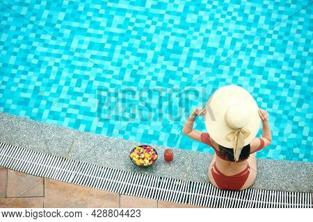 Above View Of Woman Sitting On Edge Of Poolside And Adjusting Summer Hat