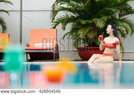 Relaxed Young Asian Woman Sitting On Poolside And Keeping Legs In Water While Drinking Refreshing Co