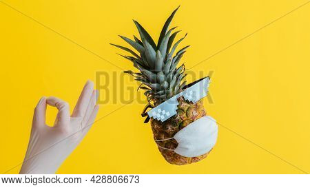 Hand In Glove Hand Shows Okay Sign. Pineapple In Medical Face Mask Sunglasses On Color Yellow Backgr