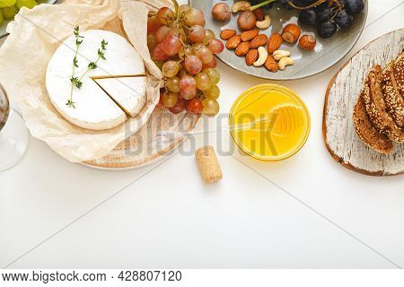 Cheese Board Appetizer And Various Delicacies Snacks Honey Nuts Grape On White Table. Gastronomy Foo