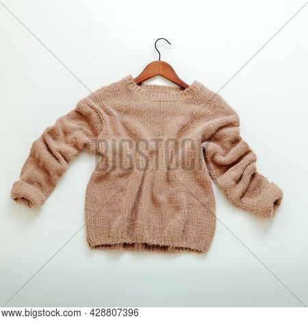 Knitted Beige Sweater On Hanger. Cashmere Sweater Flies Flat Lay On White Background. Warm Stylish H