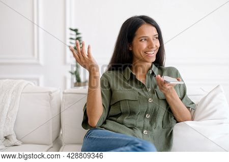 Charming Young Indian Woman Sits On The Sofa At Home, Recording And Sending Voice Message, Mixed Rac