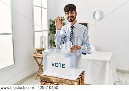 Hispanic man with beard voting putting envelop in ballot box waiving saying hello happy and smiling, friendly welcome gesture