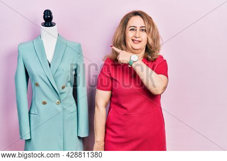 Middle age caucasian woman standing by manikin pointing aside worried and nervous with forefinger, concerned and surprised expression