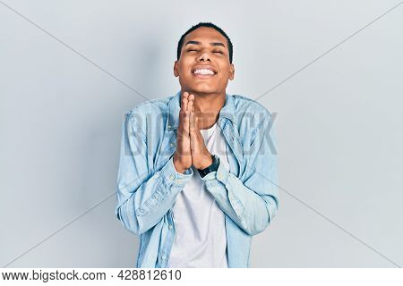 Young african american guy wearing casual clothes begging and praying with hands together with hope expression on face very emotional and worried. begging.