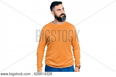 Hispanic man with beard wearing casual winter sweater smiling looking to the side and staring away thinking.