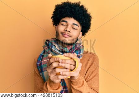 Hispanic man with afro hair smelling coffee aroma relaxed with eyes closed
