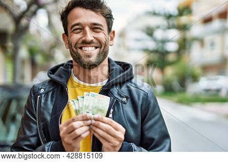 Handsome hispanic man with beard holding 500 argentina pesos banknotes outdoors