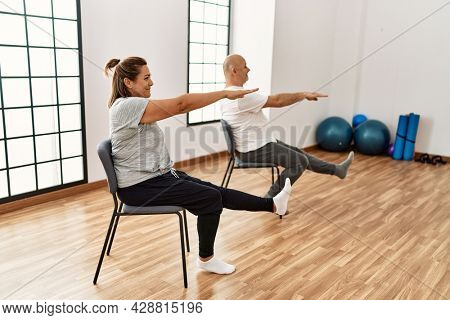 Middle age hispanic couple stretching using chair at sport center.