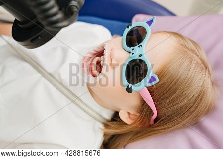 Photo Protocol In Dentistry.the Doctor Photographs The Teeth Of The Girls Child