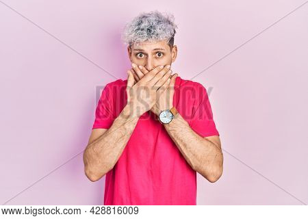 Young hispanic man with modern dyed hair wearing casual pink t shirt shocked covering mouth with hands for mistake. secret concept.
