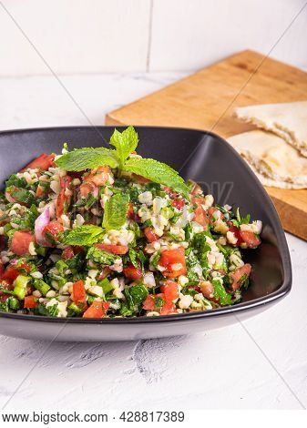 Serving Of Veggie Syrian And Lebanese Salad With Bulgur And Chopped Vegetables, Tabbouleh In A Black