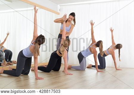 Group Of Young Sporty Sexy Women In Yoga Studio, Practicing Yoga Lesson With Instructor. Healthy Act